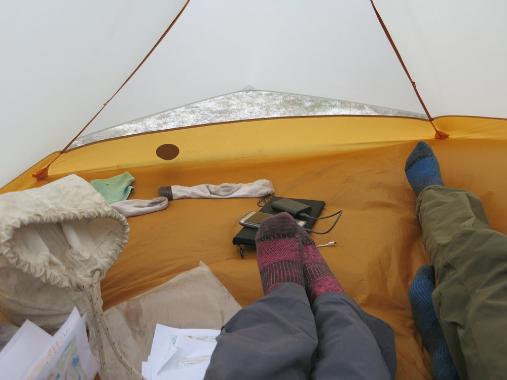 Smelly socks, our patched tent (the dark circle), and snow on the ground outside. Oh, and lots of maps.